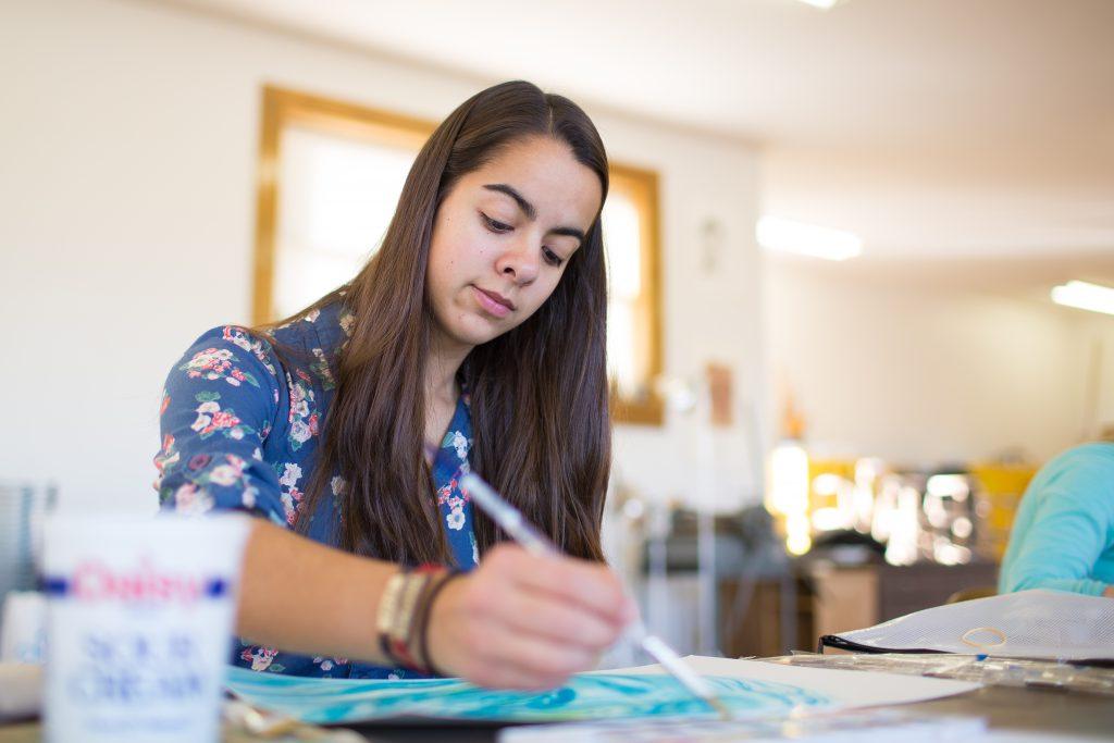 Student painting in art studio