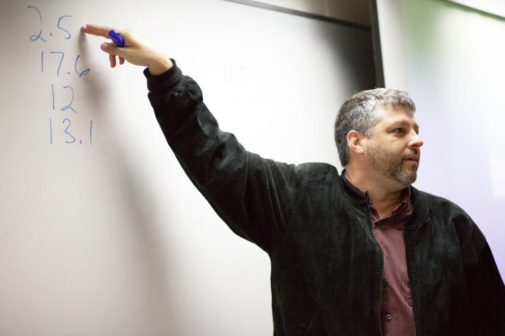 professor teaching at whiteboard